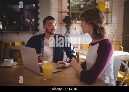 Junge Freunde sprechen beim Sitzen mit Laptop und Getränke im Coffee Shop - Stockfoto
