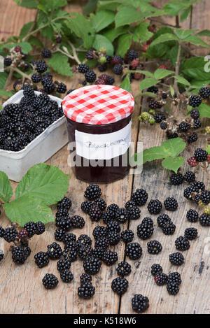 Rubus fruticosus. Hausgemachte Black jam mit einem punnet von hat Brombeeren und dornbusch Blätter auf einen hölzernen - Stockfoto