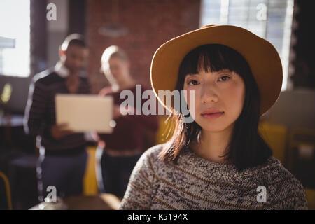 Portrait von selbstbewussten jungen Frau mit Hut stehend gegen Kollegen im Café - Stockfoto