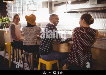 Fröhlicher junger Freunde sitzen Tabelle Zähler in Coffee Shop