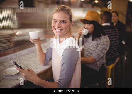 Portrait von lächelnden jungen Frau trinkt Kaffee bei der Verwendung von Mobile Phone an der Theke im Café - Stockfoto