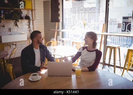 Lächelnden jungen Freunde sprechen beim Sitzen mit Laptop am Tisch im Café - Stockfoto
