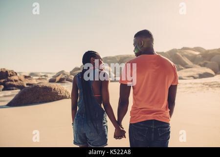 Afrikanische amerikanische Paar Hände halten und zu Fuß am Strand entlang. Mann und Frau in der Liebe ein Spaziergang - Stockfoto
