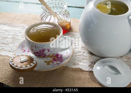 Ingwer Tee Tasse mit Honig und Wasserkocher auf sackleinen über Holz- Tabelle - Stockfoto