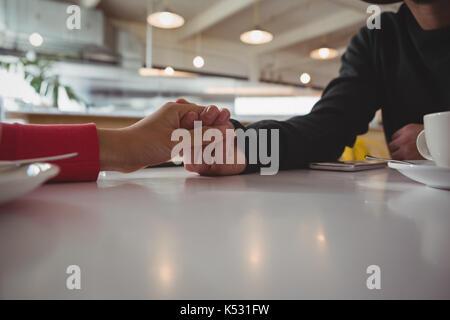 Zugeschnittenes Bild des Paares, das Hände bei Tisch im Cafe