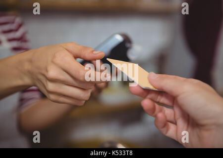 7/8 Hand des Kunden an weiblichen Besitzer im Cafe - Stockfoto