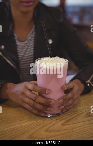 Den mittleren Abschnitt der Frau mit milchshake Glas an den hölzernen Tisch im Cafe - Stockfoto