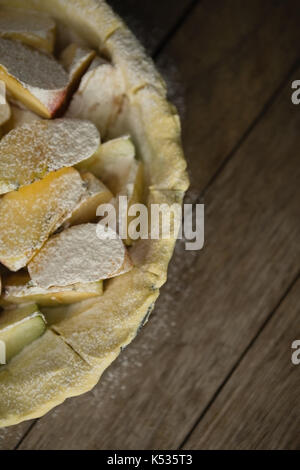 Nahaufnahme von Apfelscheiben im Teig in der Backform auf hölzernen Tisch - Stockfoto