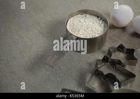 Hohe Betrachtungswinkel von Mehl in Container mit Ei und Pastry Cutters auf Tisch - Stockfoto