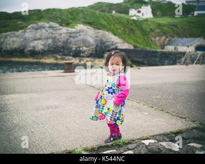 Baby Mädchen zu Fuß in den kleinen Hafen, Nordirland - Stockfoto