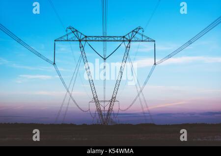 Power Line in einem Feld auf dem Hintergrund des blauen Himmels am Abend kommen über den Horizont der Sonne - Stockfoto