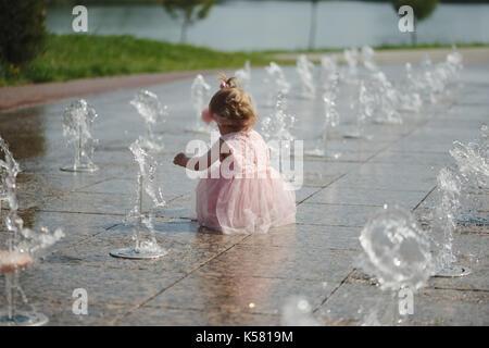 Kleines Mädchen spielt mit Wasser im Brunnen - Stockfoto