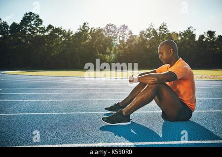 Schwerpunkt junge afrikanische männlichen Athleten in Sportkleidung alleine sitzen auf einer Laufstrecke mentale - Stockfoto