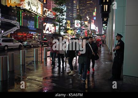 Regnerischen Nacht in Times Square, Touristen mit Sonnenschirmen gehen 7. Avenue und Broadway hell erleuchtet durch - Stockfoto