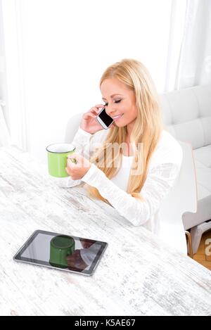 Eine schöne junge blonde Frau am Tisch mit einem Kaffee und Gespräch am Telefon Standortwahl