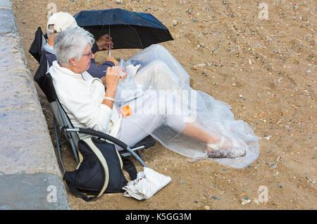 Swanage, Dorset, Großbritannien. 9 Sep, 2017. UK Wetter: Starker Regen und Donner am Swanage. Senior paar Sitzen - Stockfoto