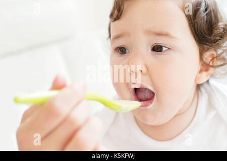 Weibliche toddler, Spoon Fed. - Stockfoto