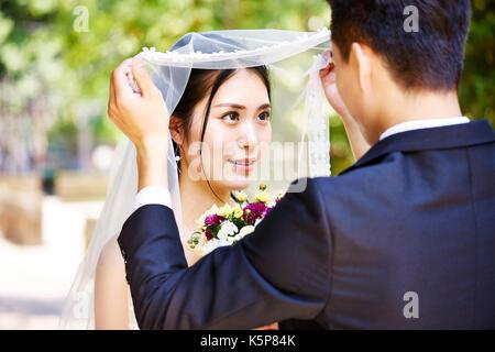 Asiatische Bräutigam anheben Bridal Veil schöne Braut zu küssen. - Stockfoto