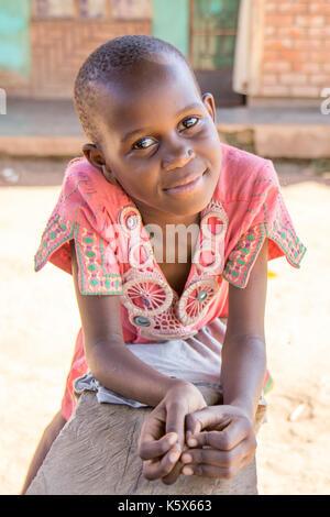 Eine schöne junge Ugandischen schwarze Mädchen stützte sich auf eine Bank. Sie hat eine ruhige, aber glückliches - Stockfoto
