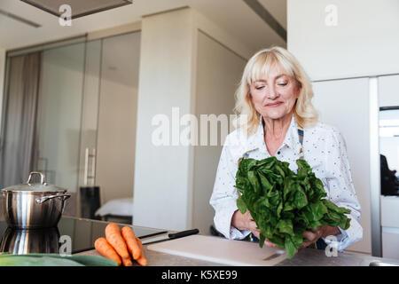 Bild von fröhlichen reife Frau zu Hause Kochen in der Küche. Neben der Suche. - Stockfoto