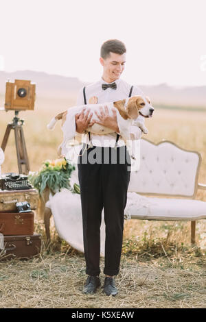 Die in voller Länge Porträt der Vintage gekleidet Bräutigam halten Sie den Hund in die Arme und sah ihn auf dem - Stockfoto