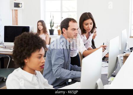 Kollegen sprechen bei der Arbeit in einem langen Großraumbüro, Nahaufnahme - Stockfoto