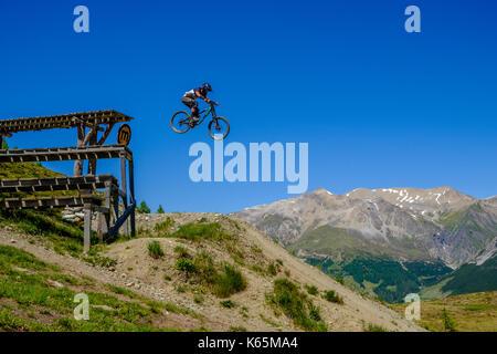 Downhill Radfahrer in Aktion Springen von einer Plattform in der motolino Bikepark - Stockfoto