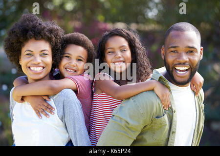 Portrait von Eltern, Kindern Piggybacks im Garten - Stockfoto