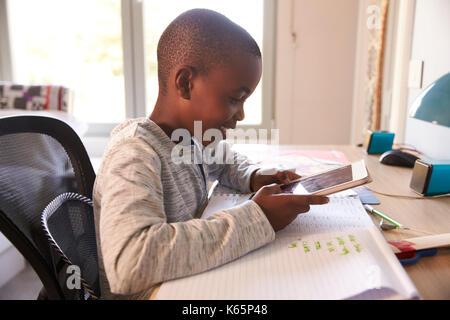 Junge in Schlafzimmer mit digitalen Tablette zu tun Hausaufgaben - Stockfoto