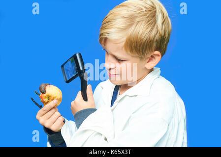 Kind die Schule junge durch Lupe auf Slug crawling Apple suchen. Suchen uäh. Weißer Hintergrund. Konzept der kleinen - Stockfoto