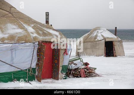 Jurten im traditionellen kirgisischen Jurtenlager während Schneesturm entlang des Song Kul / Song Kol Sees im Tian - Stockfoto