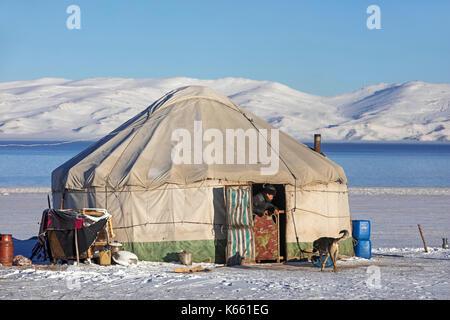 Kirgisischer Mann in Türöffnung der traditionellen Jurte im Schnee entlang Song Kul / Song Kol See im Tian Shan - Stockfoto