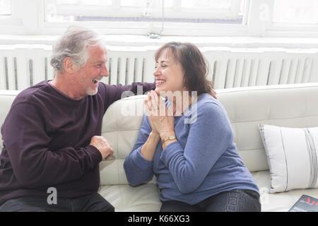 Älteres Paar sitzt auf dem Sofa und Lachen - Stockfoto