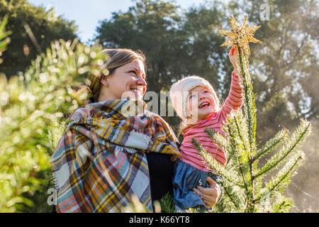 Weißen Mutter helfen Tochter Ort Sterne auf der Oberseite der Weihnachtsbaum - Stockfoto