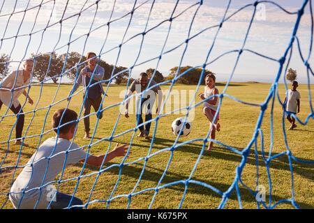 Zwei Familien Fußball im Park durch Ziel net gesehen spielen - Stockfoto