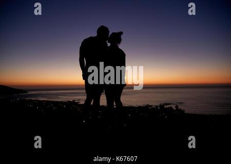 Paar stehen und Küssen durch das Meer bei Sonnenuntergang am Strand - Stockfoto