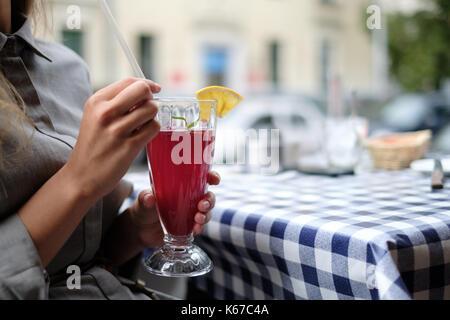Frau in einem Cafe trinken eine Cranberry cocktail - Stockfoto