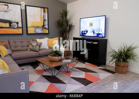 Ein graues Schnitt Couch auf einem bunten Teppich in der Nähe von einem TV-Standfuß und Beistelltisch. - Stockfoto