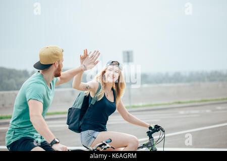 Passen Radfahrer Paar stehend auf dem Gipfel hoch fiving an einem sonnigen Tag - Stockfoto