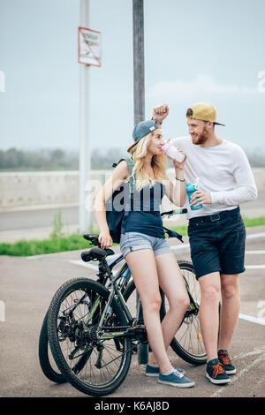 Junge hipster Paar Hand in Hand gehen auf die Wiese, erholsame und natürliche Atmosphäre ist sehr natürlich. - Stockfoto