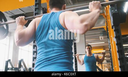 Fitnessraum - muskulöse Mann führt Kniebeugen mit Langhantel - Rückansicht - Stockfoto