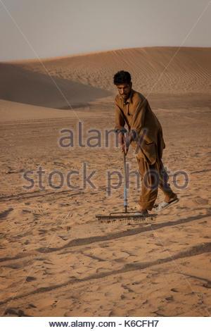 Dubai, Vereinigte Arabische Emirate - ca. August 2014: Ein Mann ist mit einem Besen den Sand der Wüste rund um Dubai - Stockfoto