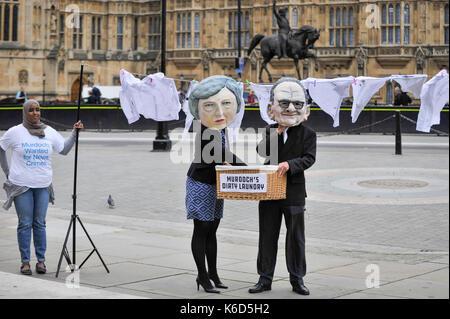 London, Großbritannien. 12 Sep, 2017. Ein paar Stand außerhalb der Häuser des Parlaments tragen eines Pappmaché - Stockfoto