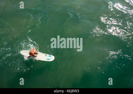 Älterer Mann paddeln Surfboard neben Pier in der Nähe der Promenade an der Goldenen Meile, Durban, Südafrika - Stockfoto