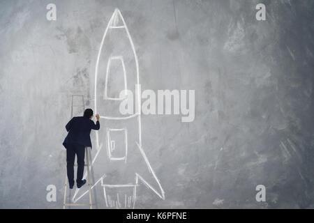 Geschäftsmann klettern Treppe Zeichnung Rakete Skizze auf Wand, Erfolg, Leader und Sieger Konzept. - Stockfoto