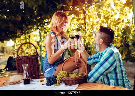 Schöne lächelndes Paar Picknick und einer Weinprobe auf einem Weingut. - Stockfoto