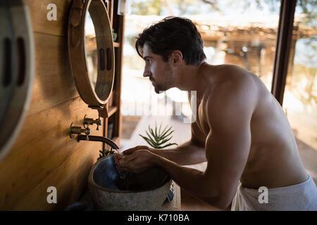 Man waschen Gesicht von Wasser im Haus während der Safari Ferienhäuser - Stockfoto