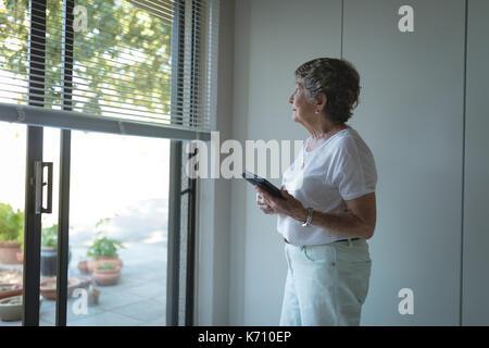 Ältere Frau durch Fenster zu hause suchen - Stockfoto