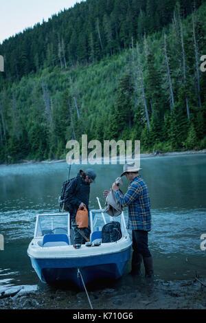 Freunde entfernen Taschen vom Boot am Flussufer gegen Bäume - Stockfoto
