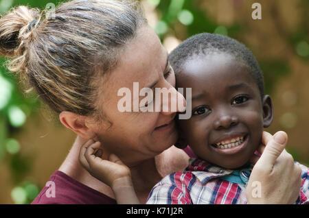 Porträt der europäischen Frau mit einem schwarzen afrikanischen Jungen - Stockfoto